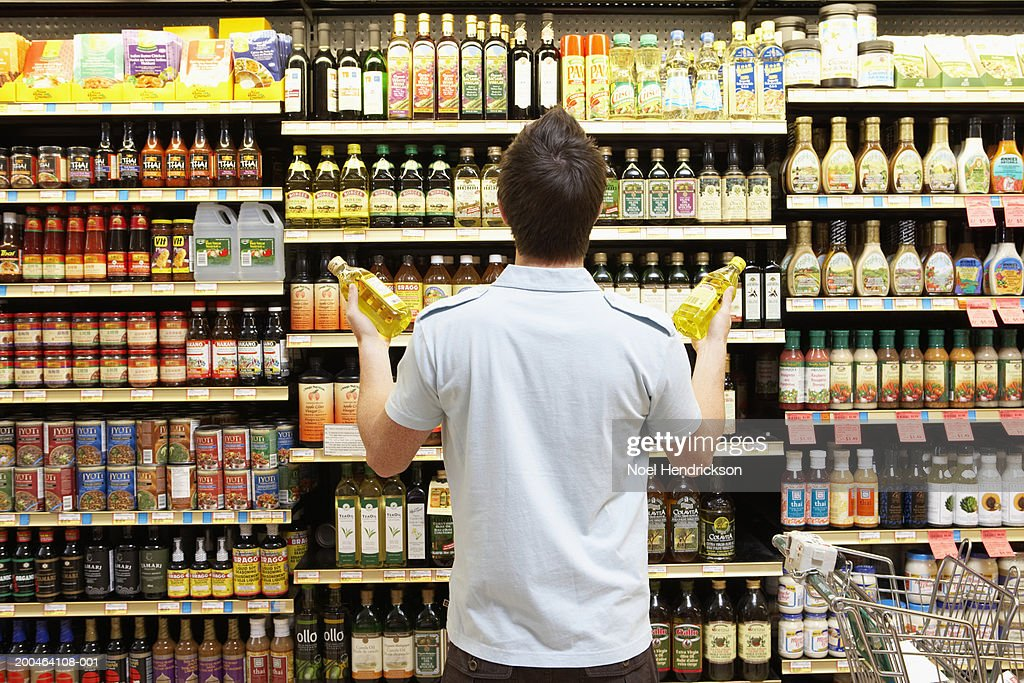 Young man looking at bottles of oil in market, rear view, close-up : Stock Photo