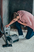 young man looking at broken vacuum cleaner at home