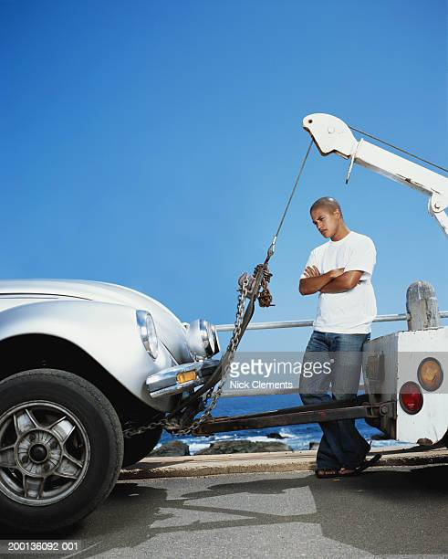Young man looking at car connected to tow truck, ocean in background