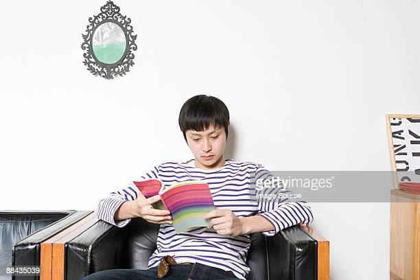 Young man looking at design book