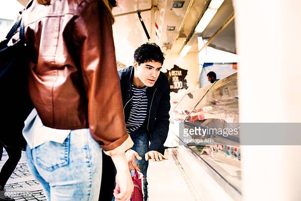 Young man looking at display while shopping with female friend at market