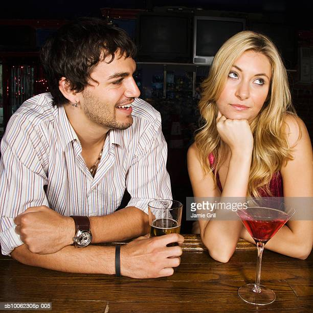Young man looking at displeased woman in bar