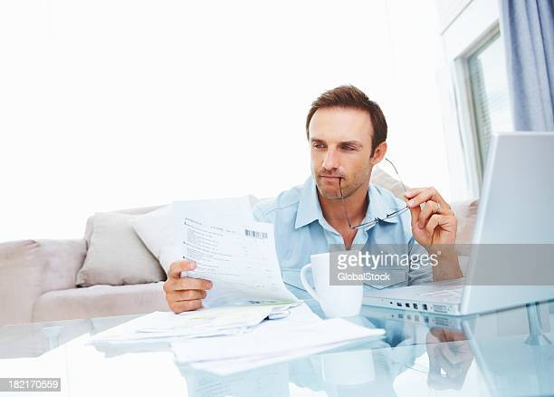 Young man looking at documents by laptop