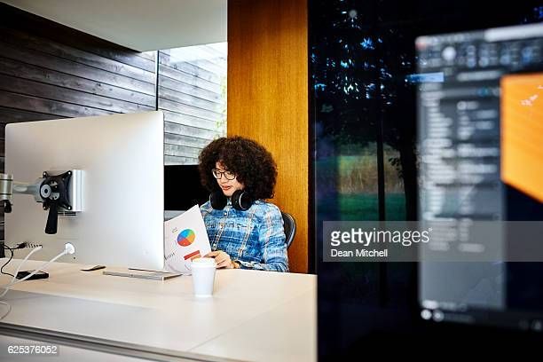 Young man looking at financial reports at workstation