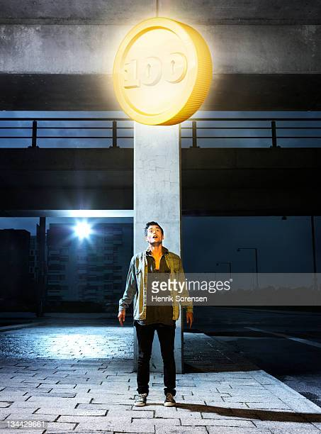 young man looking at giant coin