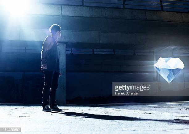 young man looking at giant glowing diamond