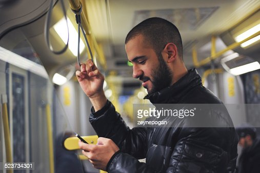 Young man looking at his smartphone in train