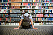 Young Man Looking at Library Shelves