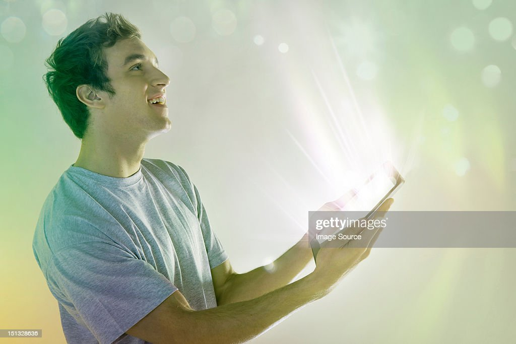 Young man looking at light coming digital tablet