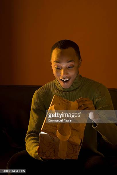 Young man looking at open gift box, mouth open, smiling