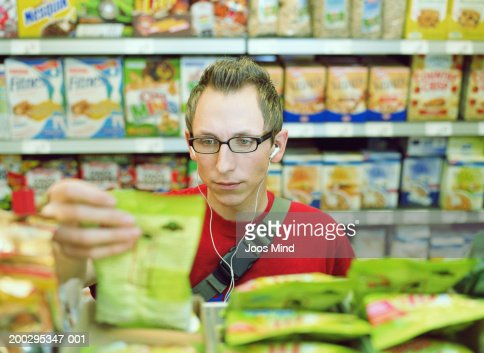 Young man looking at packet on supermarket shelf, close-up : Stock Photo