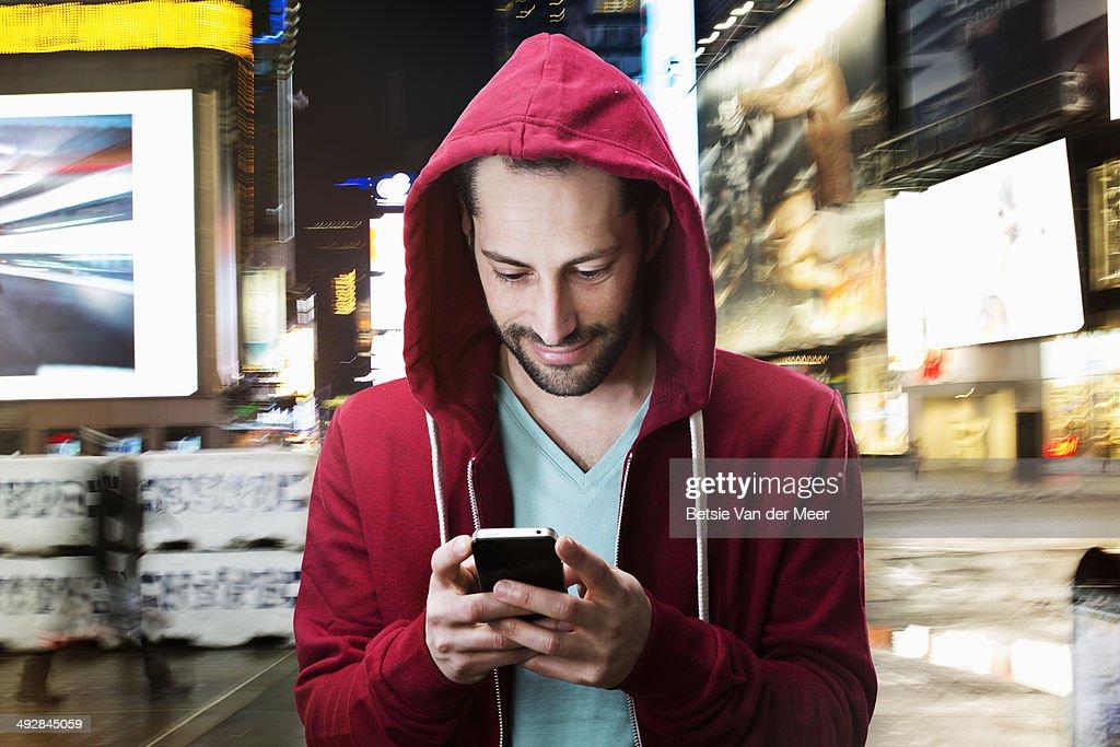young man looking at phone at night in urban city.