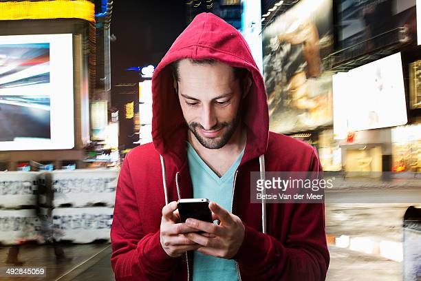 young man looking at phone at night in urban city.