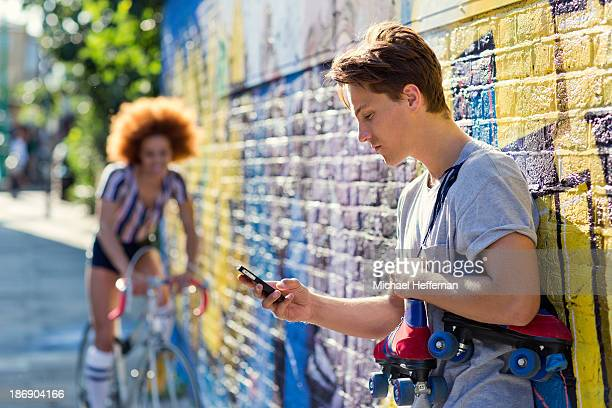 Young man looking at phone holding rollerskates