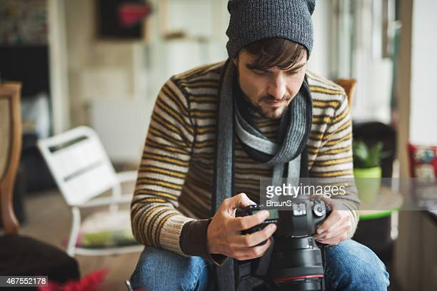 Young man looking at photos on digital camera.