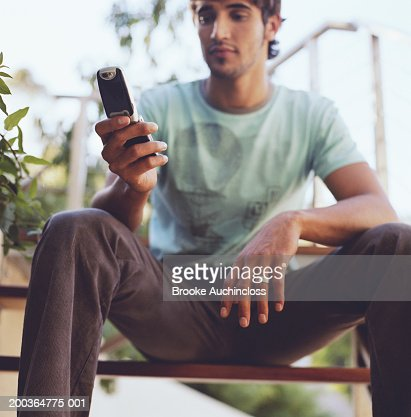 Young man looking at screen on mobile phone : Stock Photo