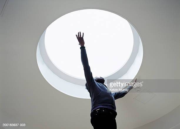 Young man looking at skylight in ceiling, arms outstretched