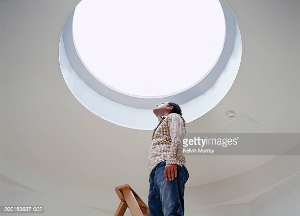 Young man looking at skylight in ceiling, standing on ladder