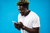 Message from you. Portrait of handsome guy in white t-shirt using mobile phone and smiling. Isolated on blue background