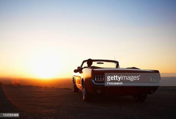 Young man looking at sunset in convertible, Arizona, USA