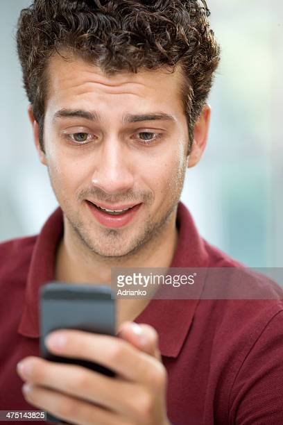 Young man looking at text message on mobile phone