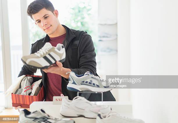 Young man looking at trainers in shoe shop, Jersey City, New Jersey, USA