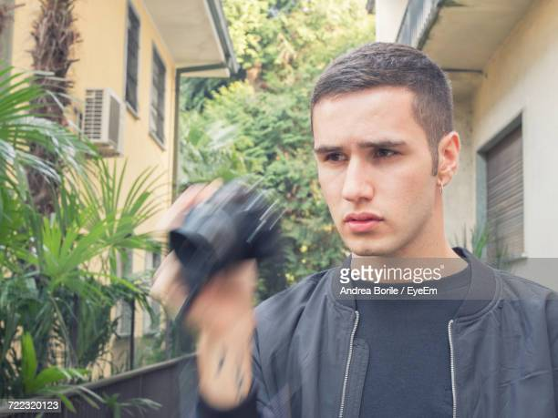 Young Man Looking Away While Holding Camera