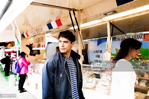 Young man looking away while shopping with friend in market