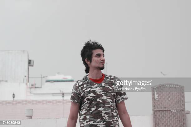 Young Man Looking Away While Standing On Building Terrace Against Sky
