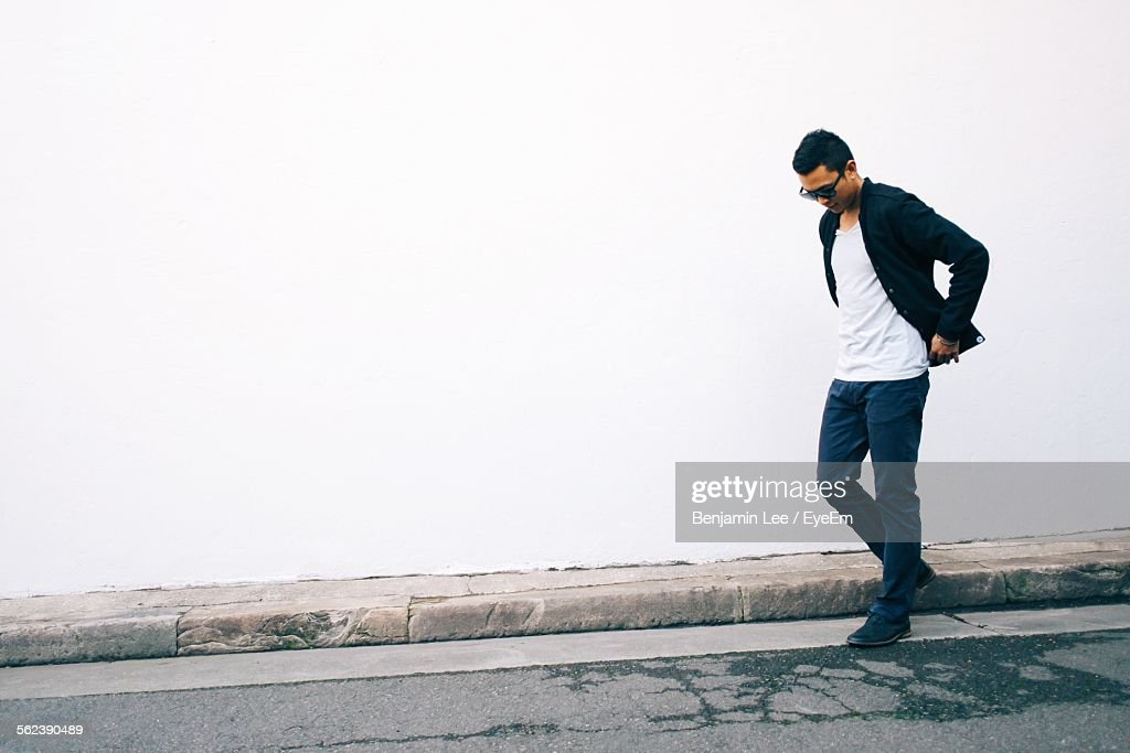 Young Man Looking Down Against White Wall : Stock Photo