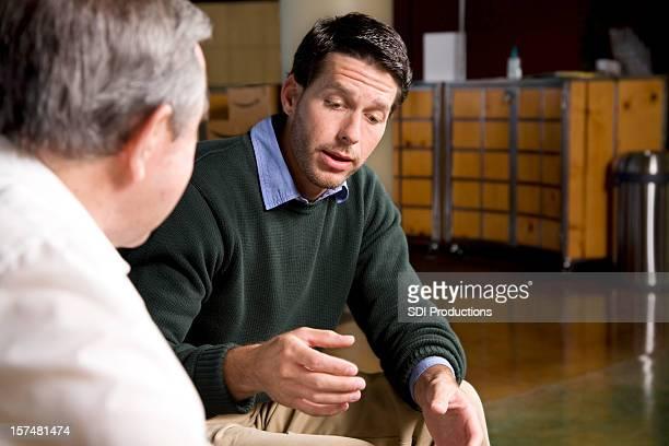 Giovane uomo guardare in basso e spiegando qualcosa a un amico