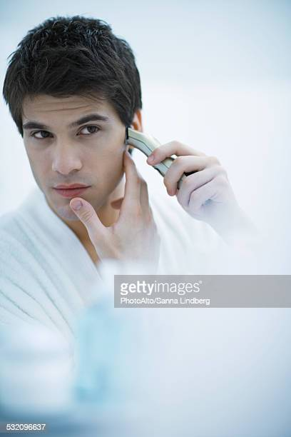 Young man looking in mirror, shaving with electric razor