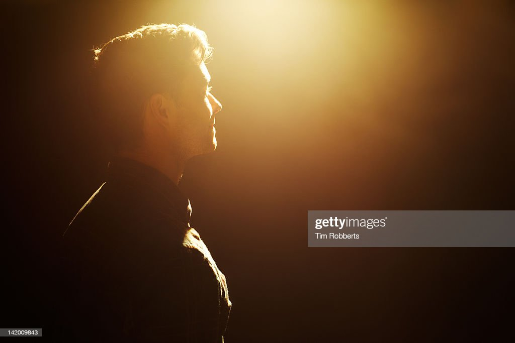 Young man looking into light. : Stock Photo