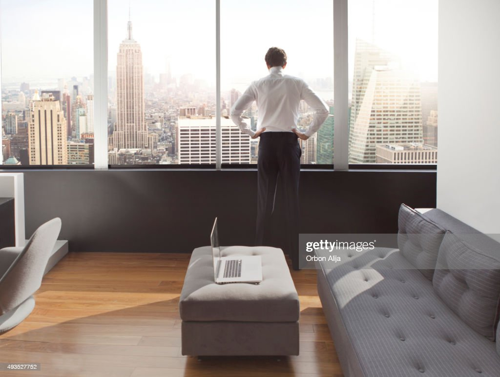 Young man looking out at city skyline : Stock Photo