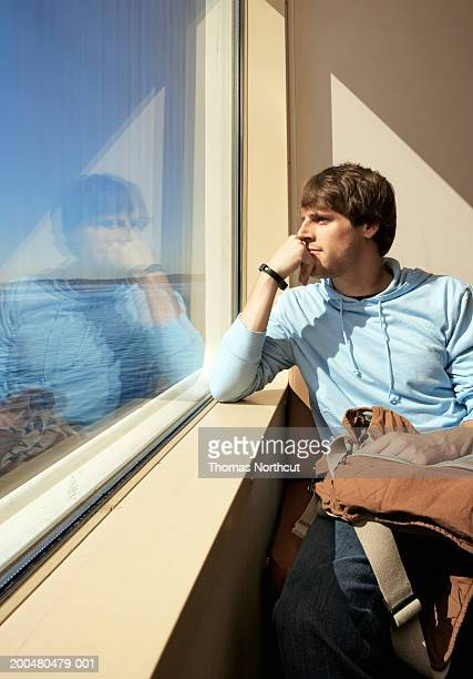 Young man looking out ferry window, resting chin on hand