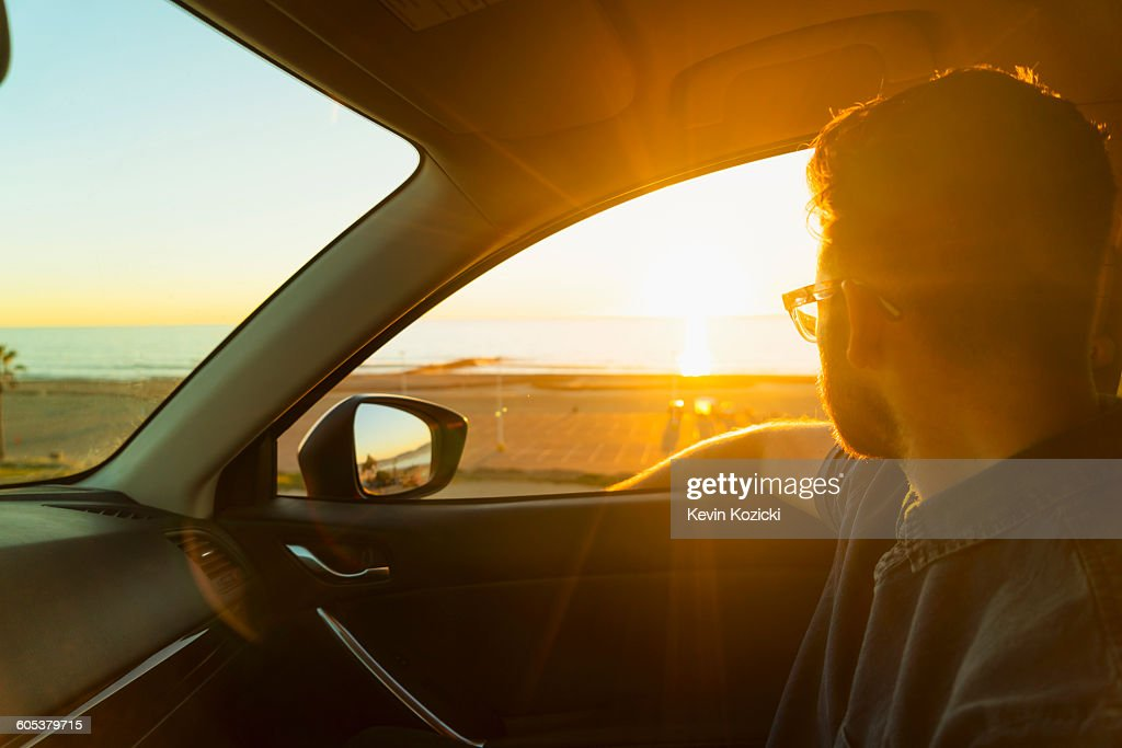 young man looking out of car window at sunset stock photo