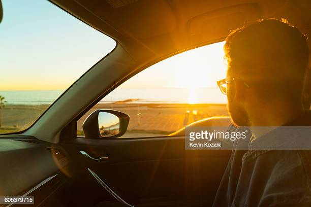 Young man looking out of car window at sunset