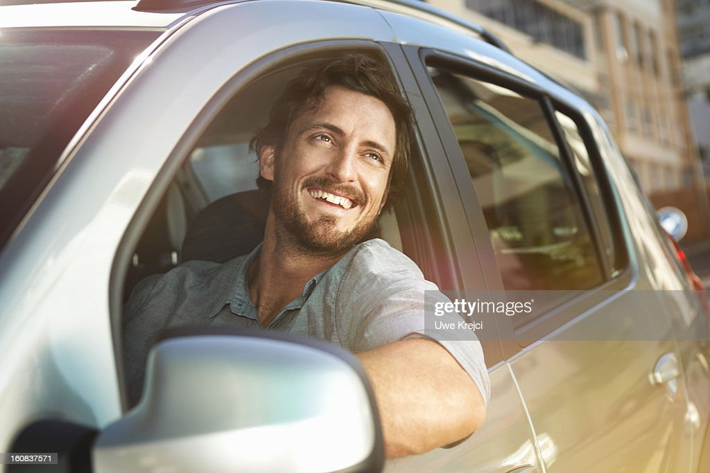 Young man looking out of car window : Stock Photo