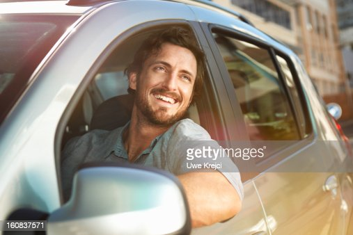 Young man looking out of car window