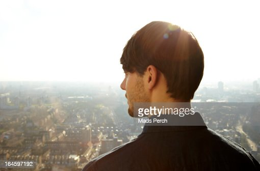young man looking out on the city : Stock Photo