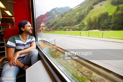 Young man looking out window of train at scenery