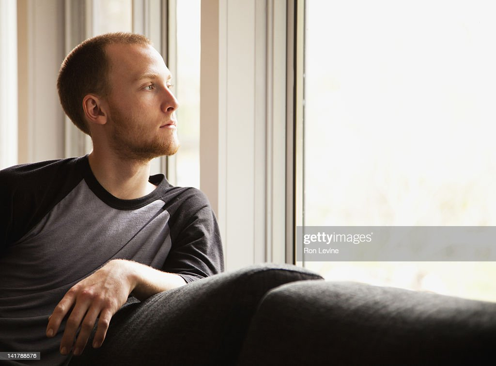 Young man looking out window : Stock Photo