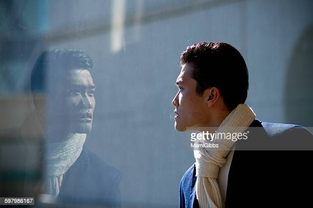 Young man looking the window