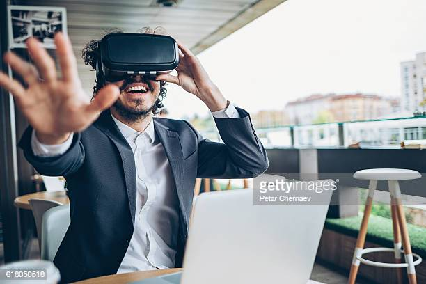 Young man looking through a virtual reality and gesturing
