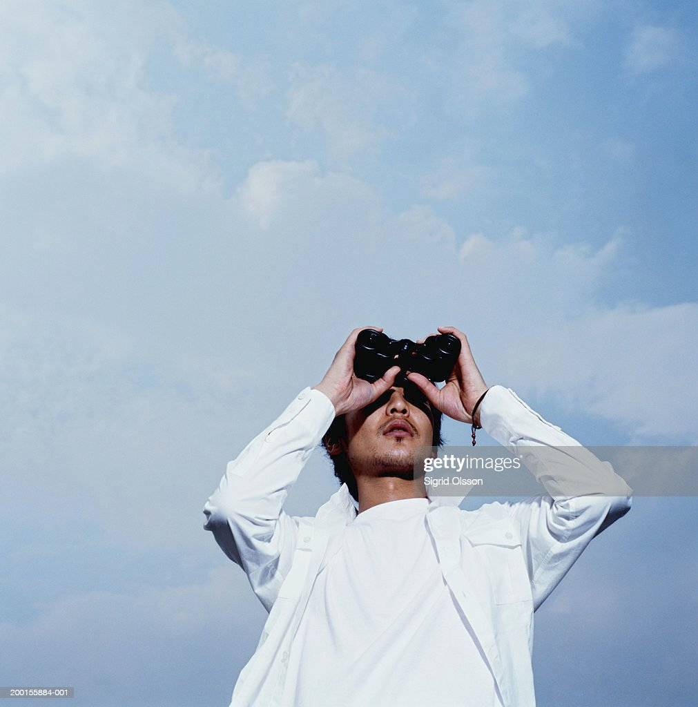 Young man looking through binoculars, low angle view : Stock Photo