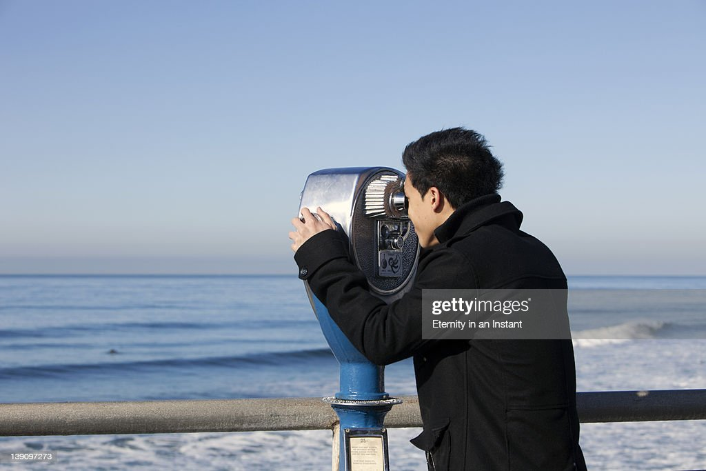 Young man looking through binoculars viewer : Stock Photo