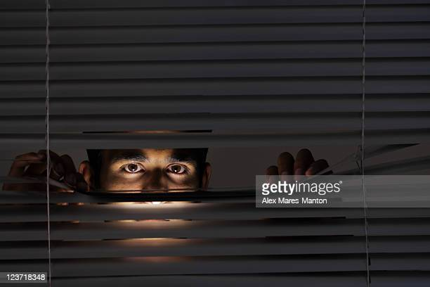 Young man looking through blinds with just his eyes visible
