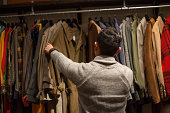 Young man looking through clothes rail in vintage shop
