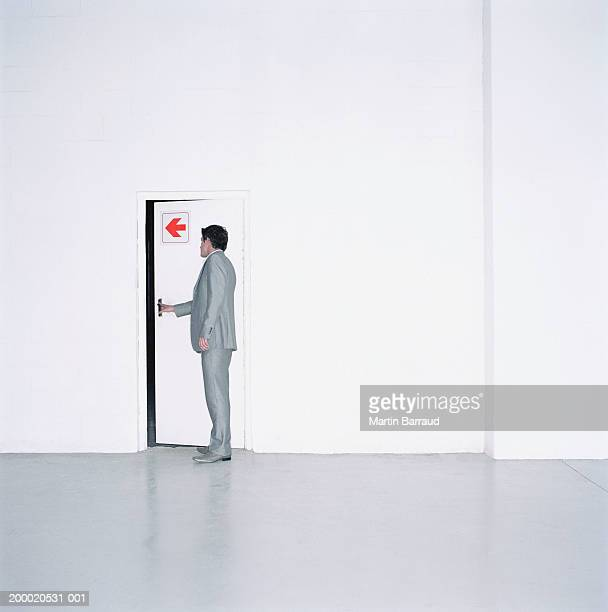 Young man looking through door with arrow on it