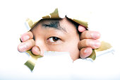 Young  man looking through ripped paper hole